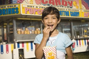 Young girl eating popcorn at a carnival